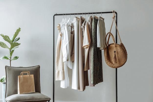 スタジオの屋内でレールにぶら下がっている服の新しいコレクション
