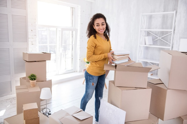 New college life. cheerful young girl taking books out of the box and smiling at the camera while unpacking, having moved into new dorm room