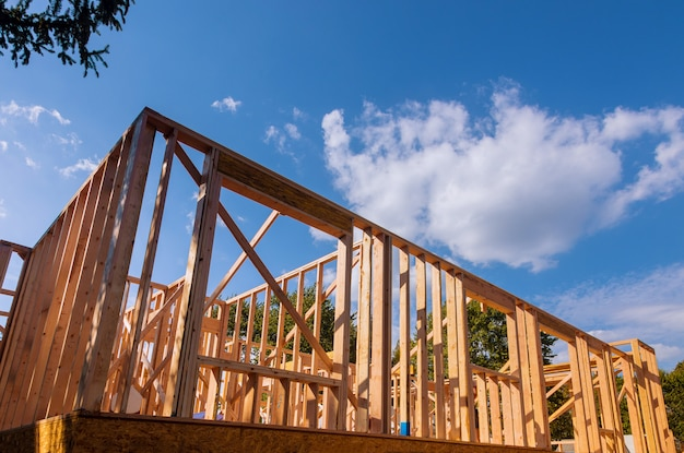 New construction home framing against a blue sky