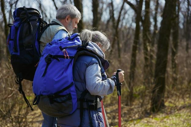 新しいクールな体験。晴れた日に木の近くの緑の芝生を歩いて観光服の男女の老家族カップル。観光、健康的なライフスタイル、リラクゼーションと一体感の概念。