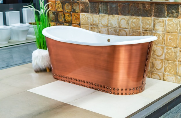 Новая медная ванна на выставке для демонстрации у зеленых насаждений