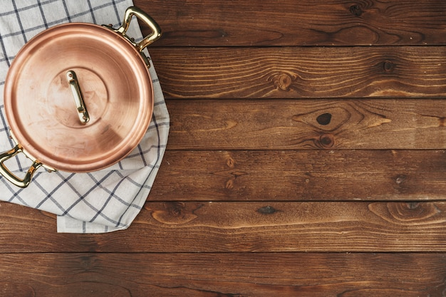 New copper cooking pot on wooden table, view from above