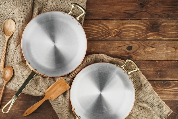 New copper cooking pot on wooden table