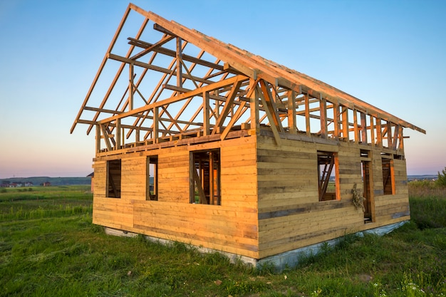New cottage of natural ecological lumber materials under construction in green field.