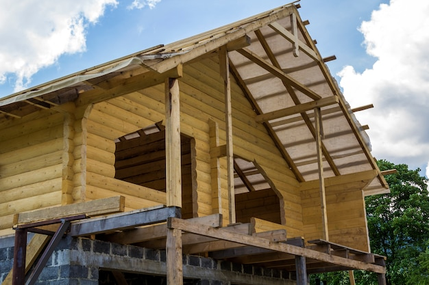 New cottage of natural lumber materials under construction. wooden walls and roof on high brick stone garage. property, investment, professional building and reconstruction concept.