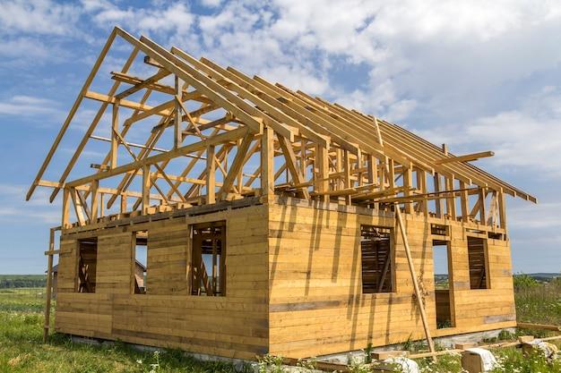 グリーンフィールドで建設中の天然の生態学的木材材料の新しいコテージ。木製の壁と急な屋根のフレーム。不動産、投資、専門的な建物と再建のコンセプト。