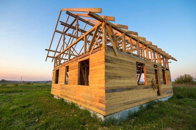 그린 필드에서 건설중인 자연 생태 목재 재료의 새로운 오두막. 나무 벽과 가파른 지붕 프레임. 부동산, 투자, 전문 건물 및 재건 개념.