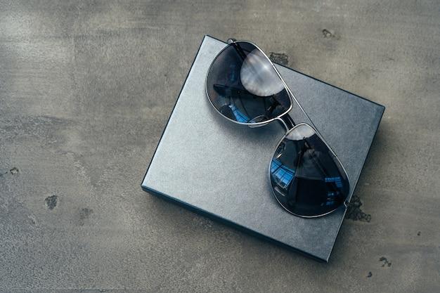 New dark aviator glasses on grey concrete background close up