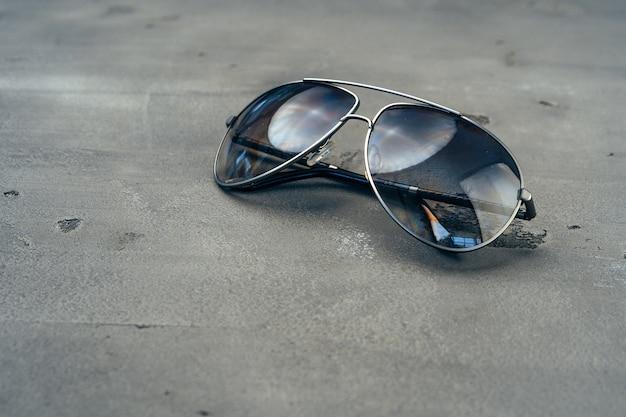 灰色のコンクリートの背景に新しい暗い飛行士のメガネ