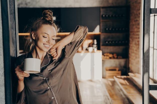 新しい日。サテンのパジャマでキッチンの出入り口に立っている間、彼女の手でコーヒーを片手にストレッチ幸せな美しいブルネットの女性は朝の日差しを楽しんでいます。人とライフスタイルのコンセプト