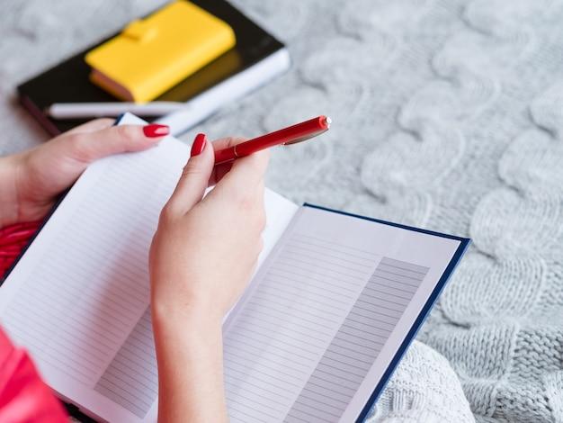 Планирование нового дня. работа по дому и покупки. женщина делает заметки в пустой тетради.