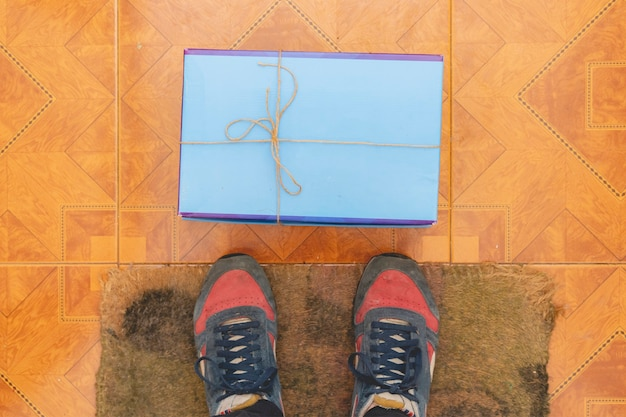 New delievered parcel lay in front of legs indoors on the floor f