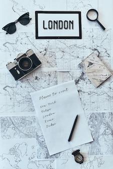 新しい目的地。地図上に置かれているさまざまな旅行用品のハイアングルショット