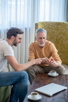 新しいデバイス。若い男が彼のお父さんに新しいスマートフォンの使い方を教えています