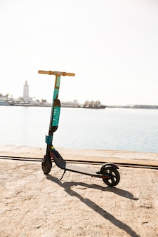 New electric scooters parked near the dock against idyllic sea