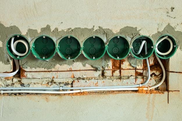 Монтаж новой электропроводки, пластиковые коробки и электрические кабели для будущих розеток на стене, концепция ремонта.
