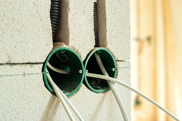 벽에 향후 콘센트 소켓을위한 새로운 전기 배선 설치, 플라스틱 상자 및 전기 케이블