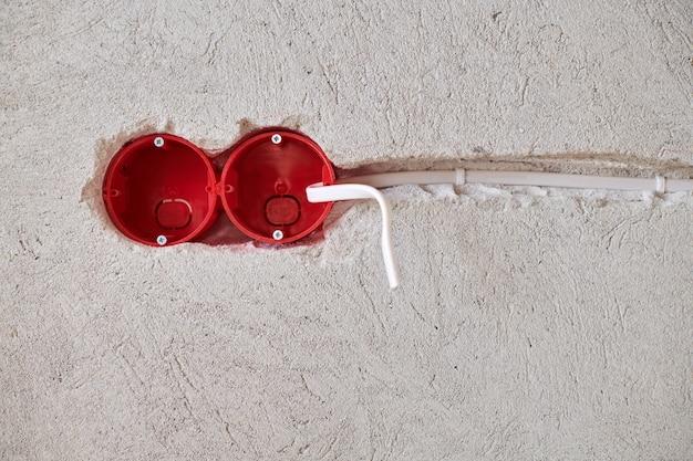 新しい電気配線の設置、漆喰壁の将来のコンセントソケット用のプラスチックソケットボックスと電線、住宅改修のコンセプト。