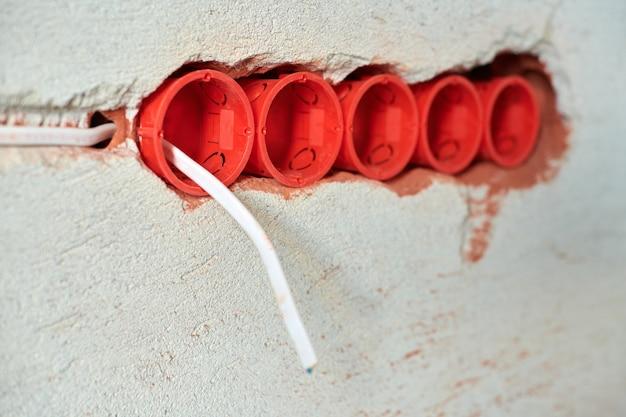 新しい電気配線の設置、漆喰壁の将来のコンセントソケット用のプラスチックソケットボックスと電線、家の改修のコンセプト。