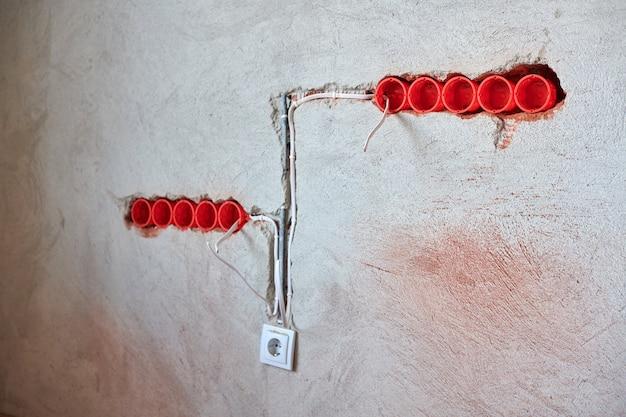 新しい電気配線の設置、プラスチック製のソケットボックス、漆喰壁の将来のコンセント用の電線 Premium写真