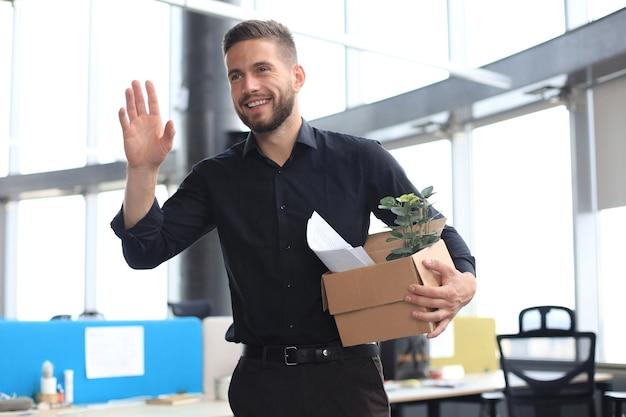現代の大規模オフィスの新入社員は、仕事用の書類や書類でいっぱいの箱を運んでいます。