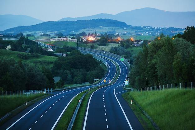 新しい空のハイウェイ。夕方の道。高速道路で車で旅行します。道路標示。夕暮れ