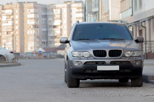 Новый дорогой серый автомобиль припаркован на мощеной стоянке перед домом. концепция транспорта и парковки