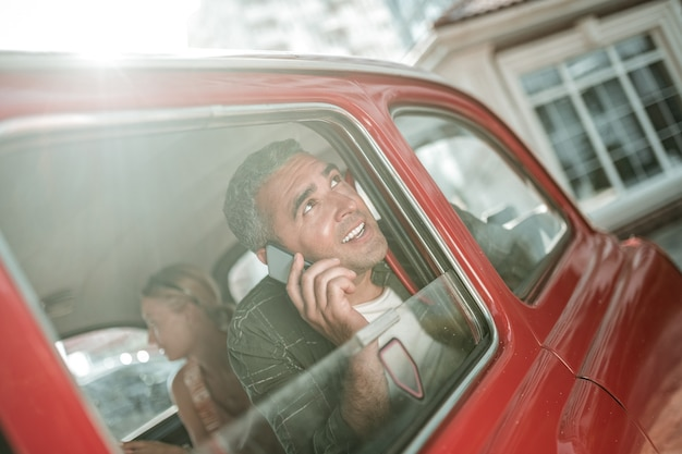 New experiences. cheerful man sitting in the car with his wife and on the phone telling his friend about his imressions in new town.