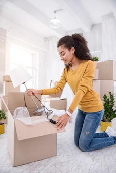 New flat. upbeat curly-haired girl taking a lamp out of the box while unpacking her belongings, having moved into a new flat