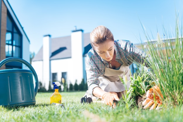 New flowers. blonde-haired woman wearing beige apron loving environment planting new flowers in the garden