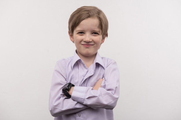 Новый гаджет. счастливый милый мальчик, стоящий с крестом на руках, нося умные часы