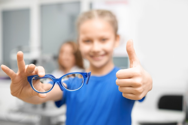 New glasses in hands of child in optical store