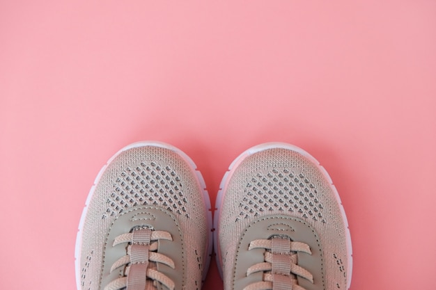 New grey sneakers on pastel pink background