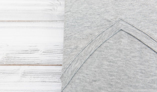 New grey v neck shirt on white wooden background