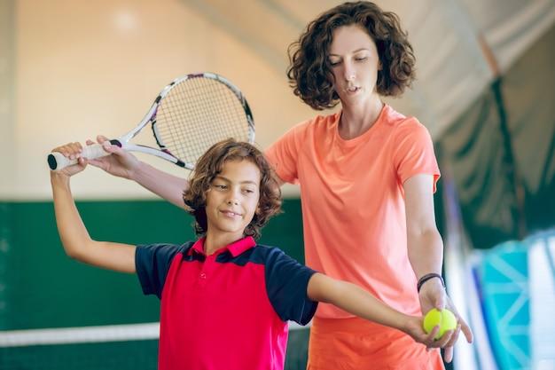 新しい趣味。彼の女性のコーチとテニスのトレーニングをしている黒髪の子供