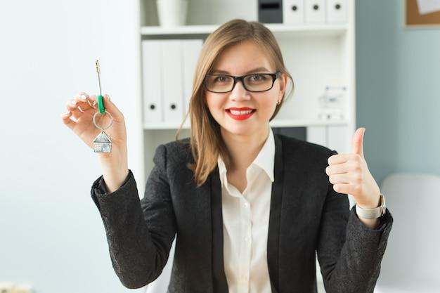 새로운 가정 및 부동산 개념-당신에게 새로운 열쇠를주는 붉은 입술을 가진 행복 부동산 여자