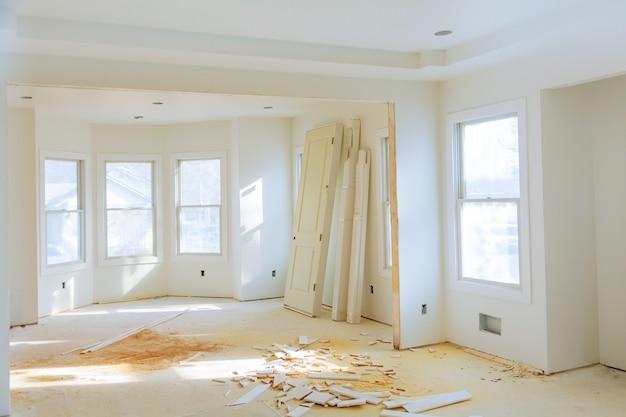 Новое домашнее строительство интерьера комнаты с незаконченными деревянными полами и двумя шкафами.