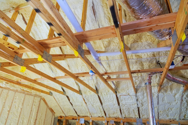 New home construction with selective focus of installed of hvac vent in roofing rafters.