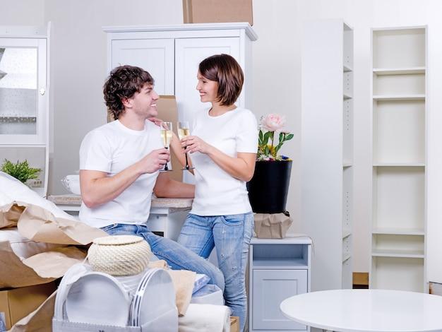 脚付きグラスで滞在する若い幸せなカップルのための新しい家