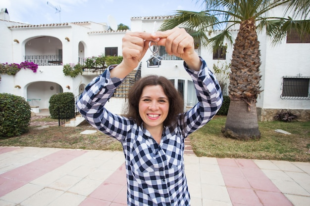New home, house, property and tenant - young funny woman holding key in front of her new home after buying real estate.