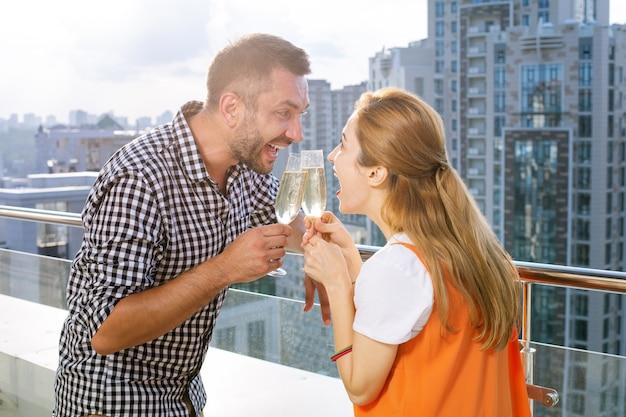 新しい家。お祝いをしながらバルコニーに一緒に立っているうれしそうな喜びの夫婦