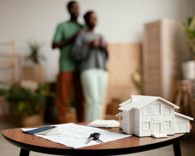 新しい家の鍵と焦点がぼけたカップルとのテーブルの計画