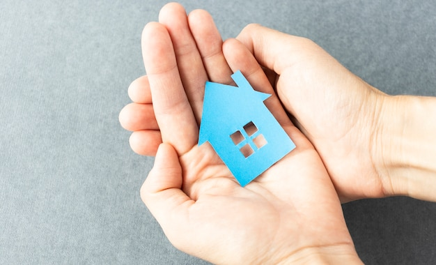 New home and real estate property concept, woman holding model house in hands.