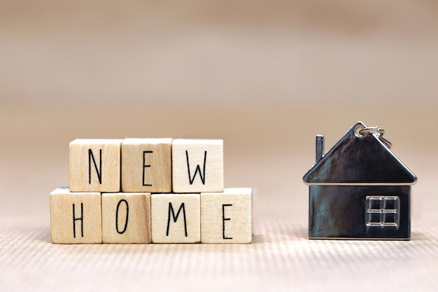 Новый домашний текст, написанный деревянными кубиками с уютным домиком