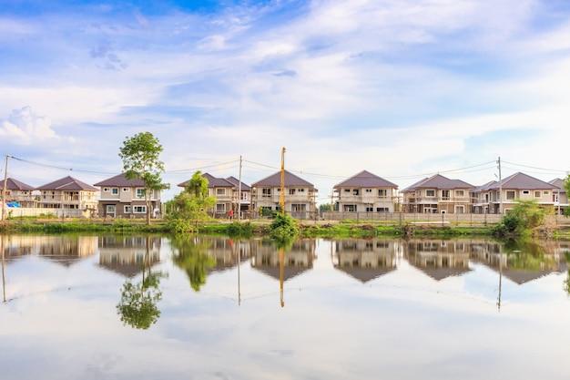 雲と青空と住宅団地建設現場で湖の水と新しい家を建てる反射