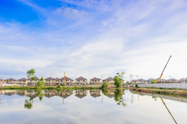 New house building reflection with water in lake at residential estate construction site with clouds and blue sky