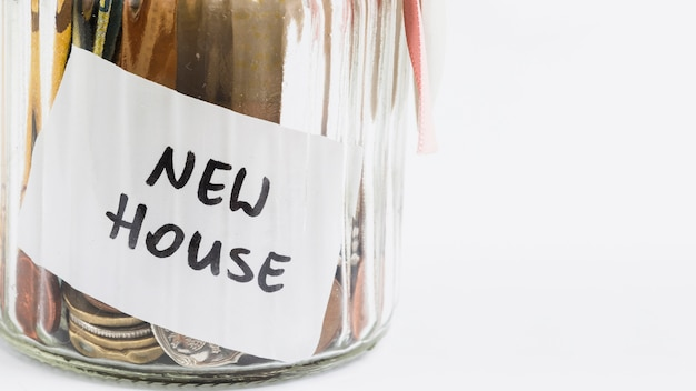 New house label on glass jar with coins against white background