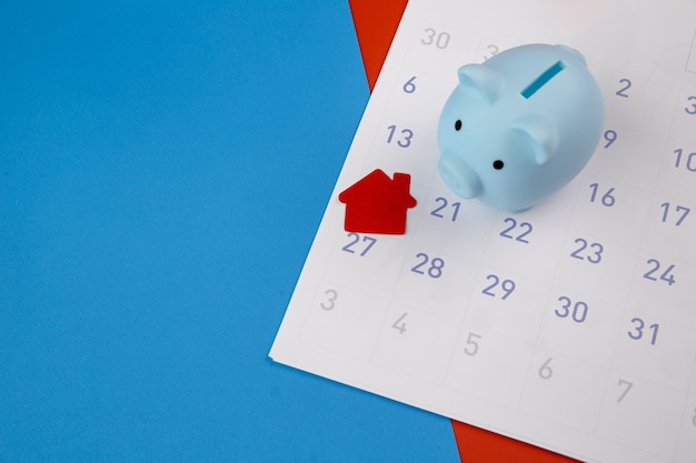 New house purchase, mortgage schedule reminder or real estate payment day, house and piggy bank