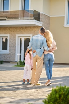 New house. standing with his back to camera man blonde woman and little girl hugging near new house on warm sunny day
