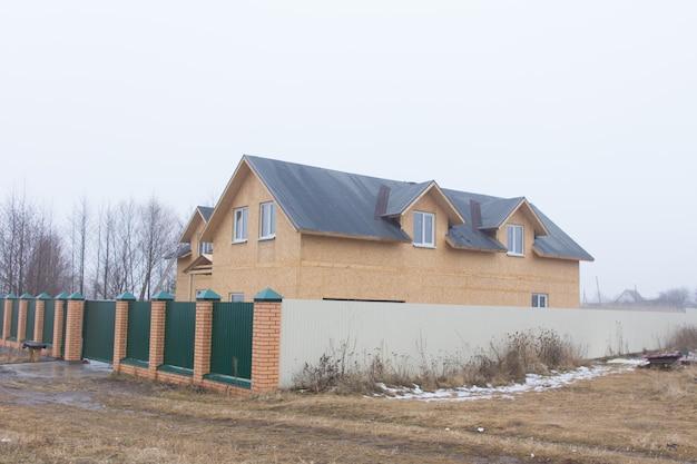 寒い霧の灰色の冬の日に見た泥だらけの田舎道にドーマー窓のセキュリティ柵と壁のある新しい家